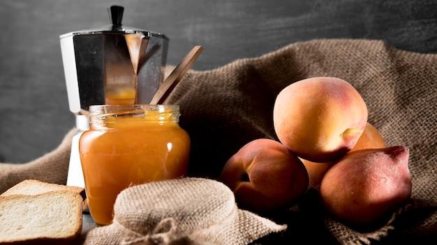 Geléia de pêssego em jarra com pêssegos e chaleira