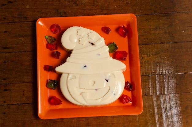 Geléia em mosaico em forma de abóbora com chapéu em um prato laranja e quadrados de gelatina colorida Foto Premium