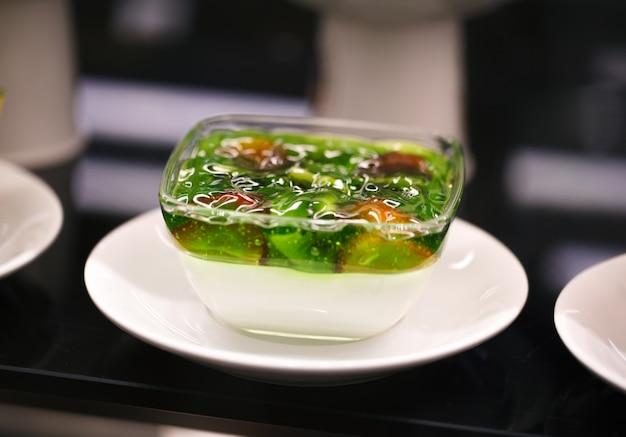 Geléia em uma tigela de kiwis com morangos, em um prato