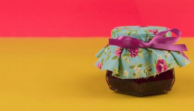 Geléia na panela isolada em fundo colorido. tendência de pastel de cores frescas. espaço para texto