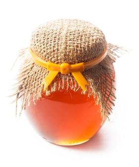 Geléia ou mel em uma jarra em fundo branco