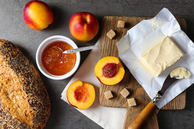 Geléia saborosa na tigela, pêssegos maduros, manteiga, biscoitos e pão fresco em close-up do tablet de madeira