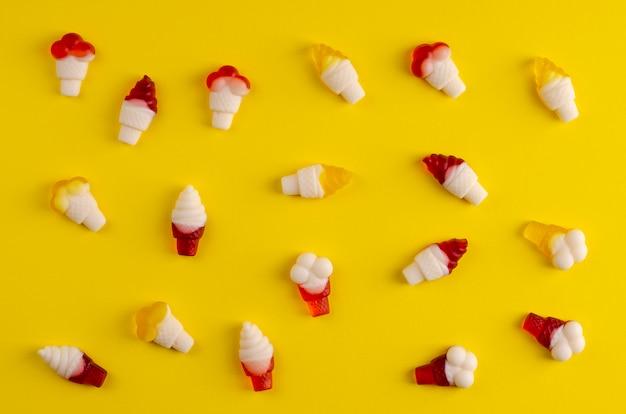 Geléias coloridas em forma de cones de sorvete no fundo amarelo no plano lay
