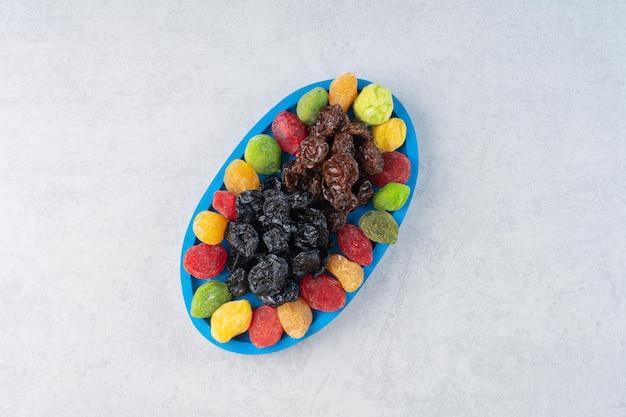 Geléias de frutas secas multicoloridas isoladas na superfície do concreto.