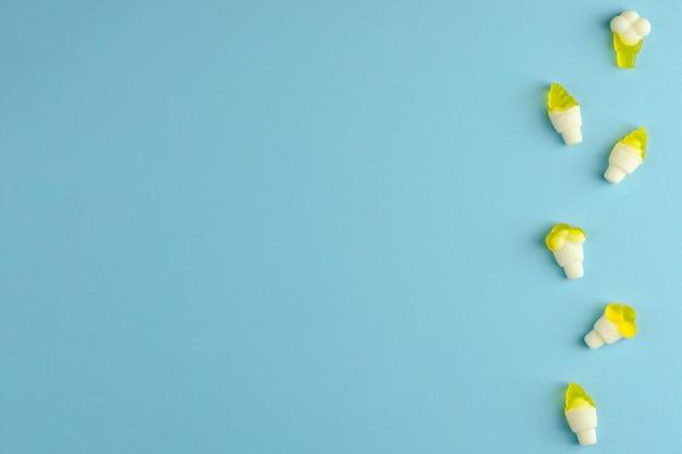 Geléias de goma em uma linha no fundo azul pastel