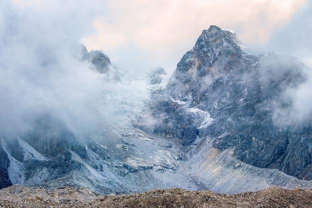Geleira e montanhas nas nuvens. parque sagarmatha, rota para o acampamento base do everest. nepal