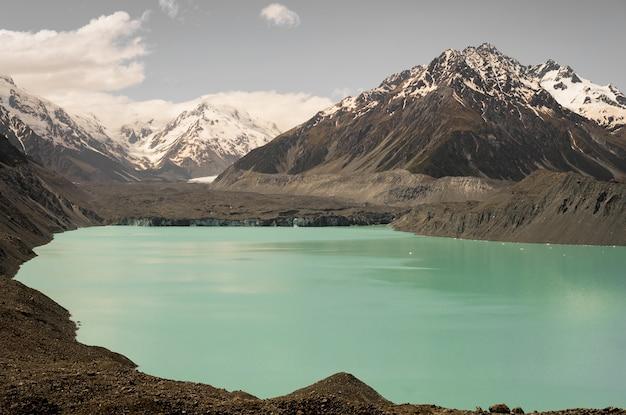 Geleira hooker cercada por rochas cobertas de neve na nova zelândia