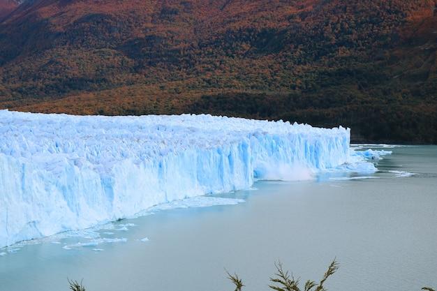 Geleira perito moreno com o gelo parindo no lago, patagônia, argentina