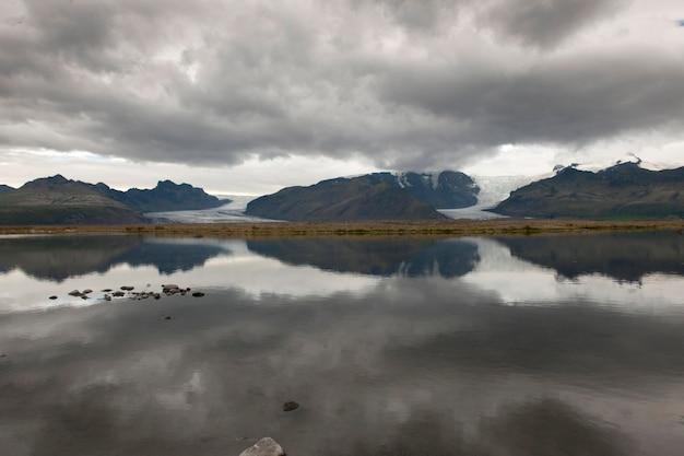 Geleiras de montanhas cinzentas e nuvens escuras refletidas no lago