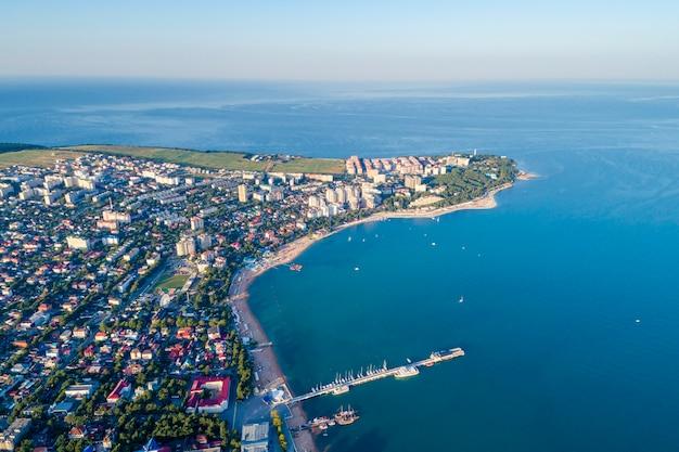 Gelendzhik atirando de um drone. um íngreme e grosso promontório com um farol e a parte central da cidade com um cais marítimo. uma vasta praia citadina, várias casas, navios no mar e no cais.