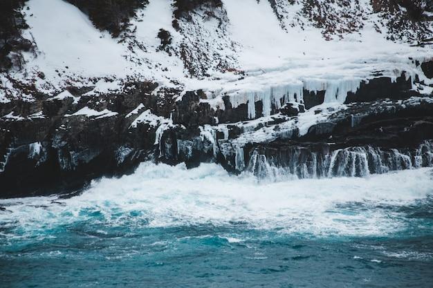 Gelo branco em montanha rochosa perto do corpo d'água durante o dia