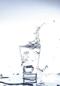 Gelo caindo e salpicos de água no copo com reflexo na mesa de espelho