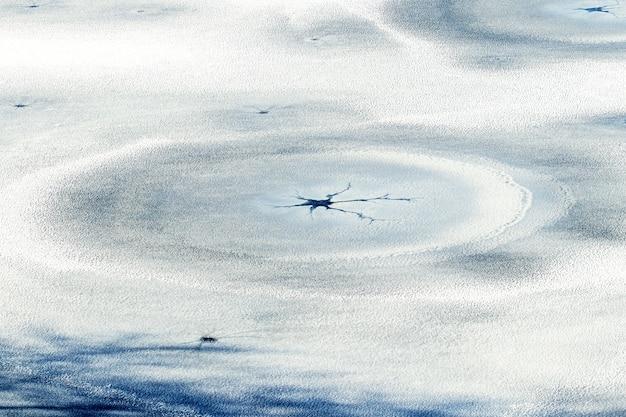 Gelo coberto de neve com rachaduras e círculos concêntricos