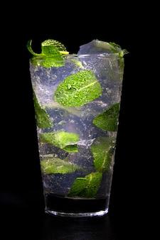 Gelo e hortelã cocktail no preto. mojito com gelo.