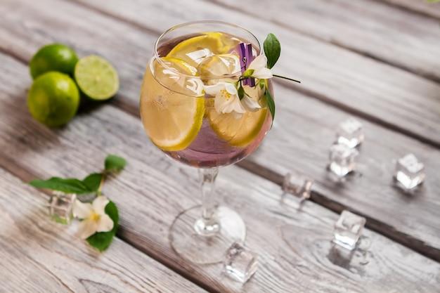 Gelo e limão dentro da bebida. fruta fatiada e flor pequena. tom collins com gim caro. suco misturado com água fria.