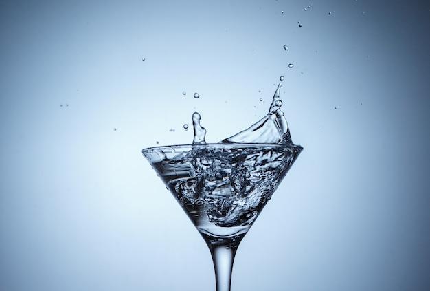 Gelo em copo com respingos de água na superfície azul