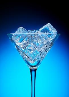 Gelo em um copo de martini em um fundo azul com um gradiente