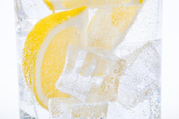 Gelo, fatias de limão e água limpa em um copo.