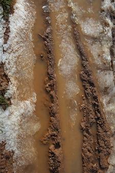 Gelo na lama estrada de solo de barro vermelho com linhas de pneus