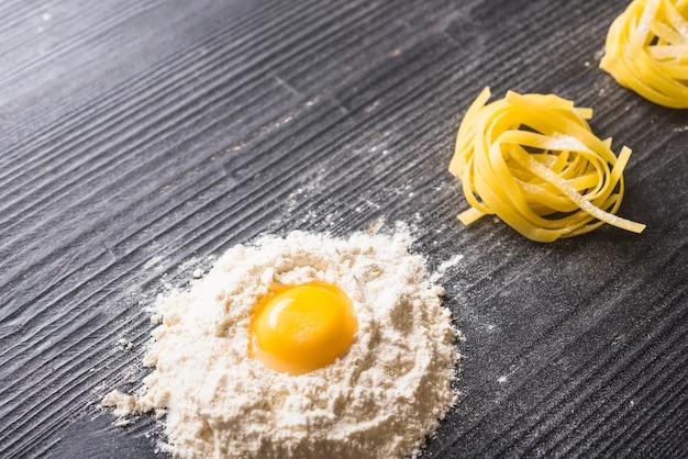 Gema de ovo com farinha branca e tagliatelle cru em pano de fundo preto de madeira