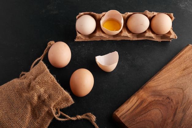 Gema de ovo dentro da casca de ovo em fundo preto na bandeja de papelão.