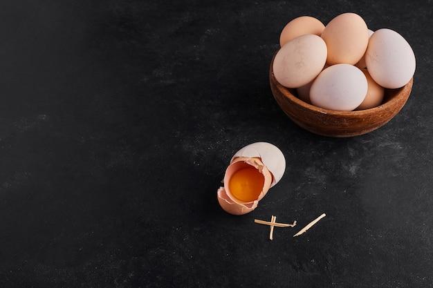 Gema de ovo dentro de uma casca de ovo quebrada com um copo de madeira com ovos de lado.