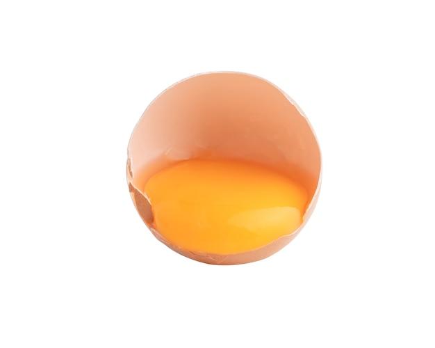 Gema de ovo em uma casca quebrada isolada na superfície branca com traçados de recorte