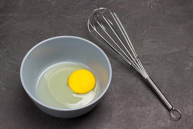 Gema de ovo em uma tigela e batedor de metal. cozinhando. fundo preto. vista do topo