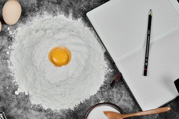 Gema de ovo na farinha, caderno e lápis na mesa de pedra.
