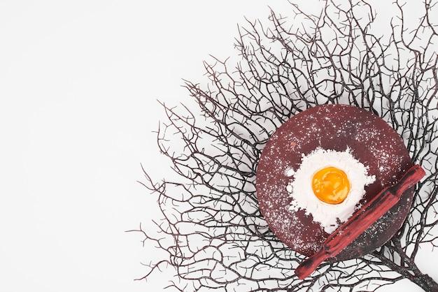 Gema de ovo na farinha em uma travessa de madeira.