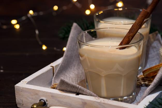 Gemada branca caseiro do feriado com uma vara de canela na obscuridade com bokeh claro. bebida de natal
