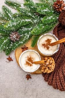 Gemada caseira com canela em vidro. sobremesa típica de natal. evergreen brunch de abeto, cones, manta aconchegante, neve artificial.