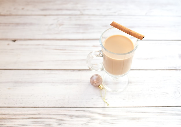 Gemada de inverno tradicional em caneca de vidro com leite, rum e canela, decorações de natal.