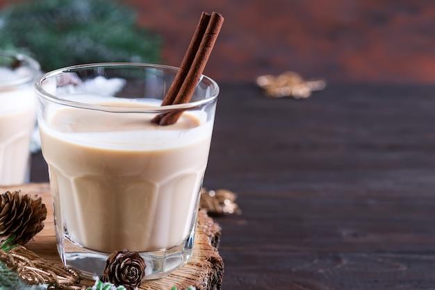 Gemada natal coquetel de leite com canela, servido em dois copos em uma tábua de madeira com ramo de abeto e pinha no escuro de madeira