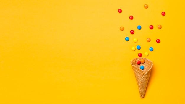 Gemas coloridas derramadas de cone de waffle em pano de fundo amarelo