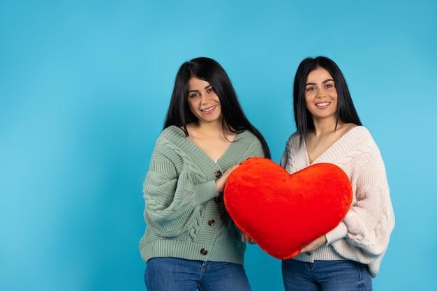 Gêmeas com um grande coração vermelho de pelúcia no dia dos namorados