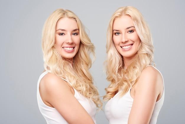 Gêmeas loiras em pé frente a frente