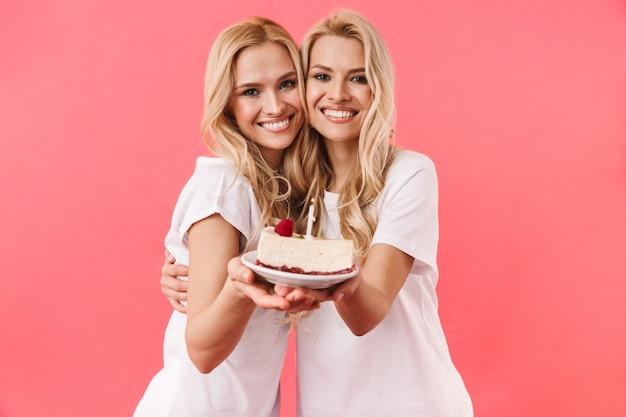 Gêmeas loiras satisfeitas vestindo uma camiseta comemorando com bolo de aniversário e olhando para a frente sobre a parede rosa