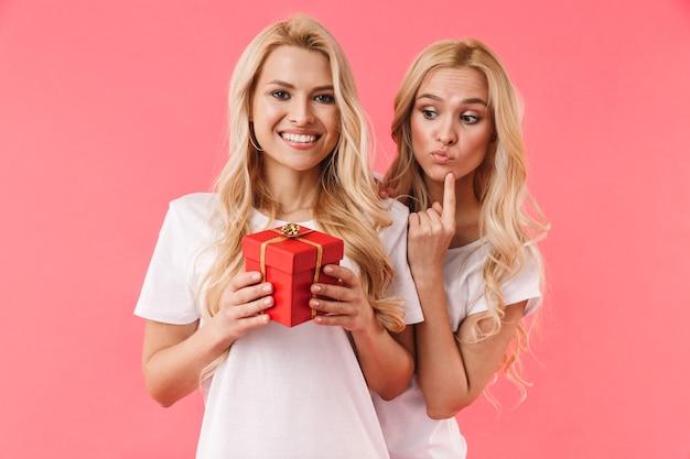 Gêmeas loiras sorridentes vestindo camisetas comemorando com uma caixa de presente na parede rosa