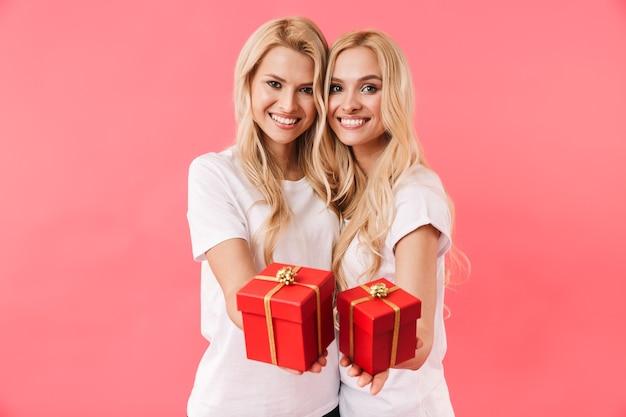 Gêmeas loiras sorridentes vestindo camisetas e dando caixas de presente para a câmera sobre a parede rosa