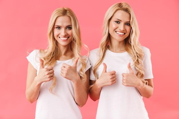Gêmeas loiras sorridentes vestindo camisetas mostrando os polegares para cima e olhando para a frente sobre a parede rosa