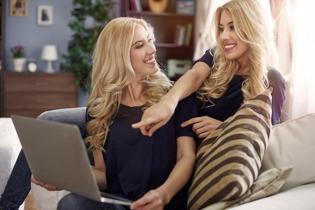 Gêmeas louras usando laptop em casa
