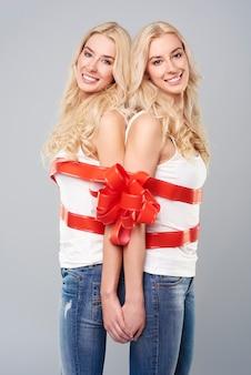 Gêmeos alegres unidos por uma fita vermelha