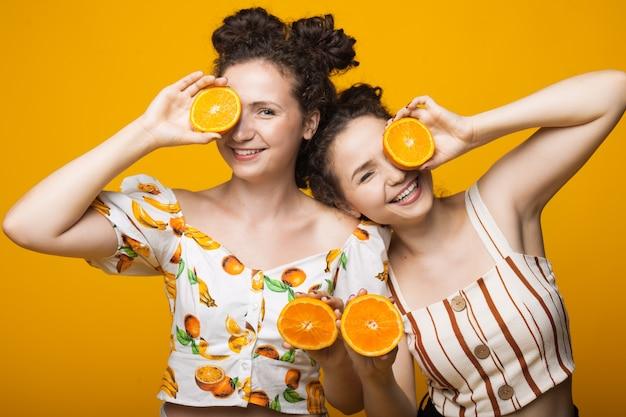 Gêmeos caucasianos cobrindo os olhos com laranjas e sorrindo
