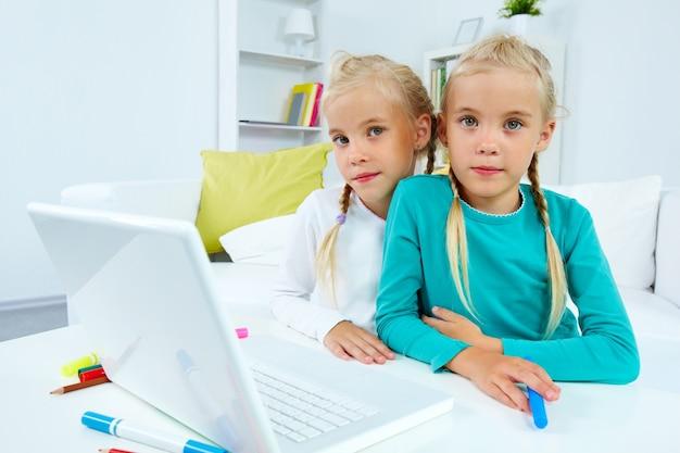 Gêmeos criativas de estar com laptop