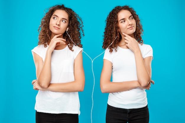 Gêmeos da mulher ouvindo música em fones de ouvido, pensando sobre azul.
