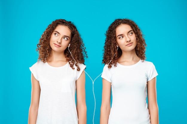 Gêmeos da mulher ouvindo música em fones de ouvido, sorrindo sobre azul.