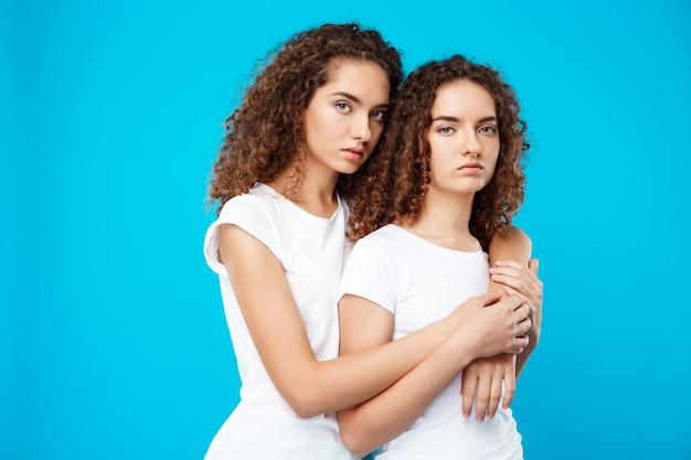 Gêmeos de duas meninas, abraçando sobre parede azul