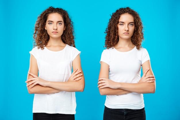 Gêmeos de duas meninas posando com os braços cruzados sobre parede azul