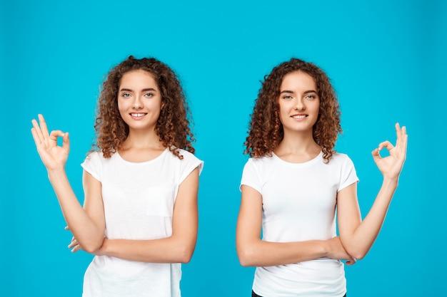 Gêmeos de duas mulheres sorrindo, mostrando bem sobre azul.
